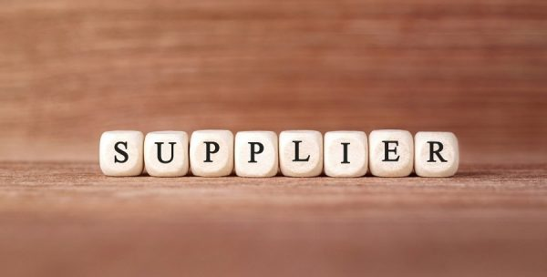 "Building materials supplier. White blocks spell ""supplier"" in black text. They are on a wood grain table with a wood grain blurred background."