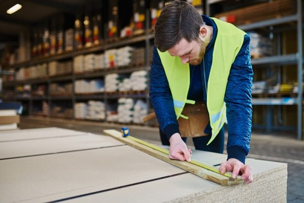 Construction products image for page. Young man in warehouse. He's measuring a piece of wood with a measuring tape. He's wearing a yellow vest.