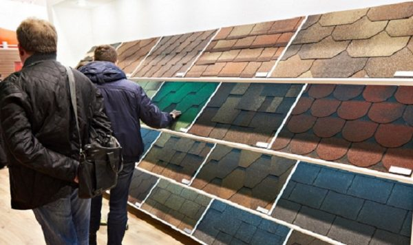 Best shingles for roofing jobs image shows two men standing in aisle facing away. They're shopping for roof shingles of different colors that are on shelves.