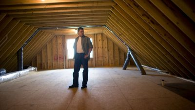 Impact of attic insulation image shows man standing on sub floor in unfinished, non-insulated attic.