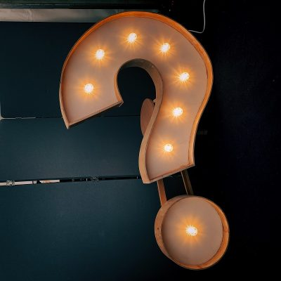 Buying roofing supplies image shows a gold neon light shaped in a question mark.